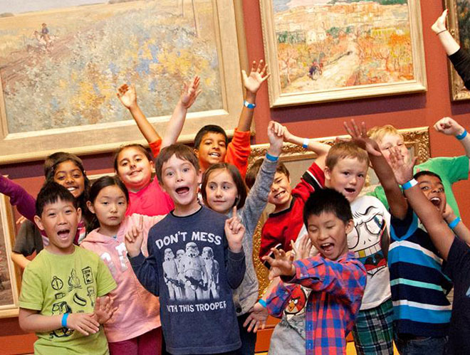 group of school children with arms in the air in gallery